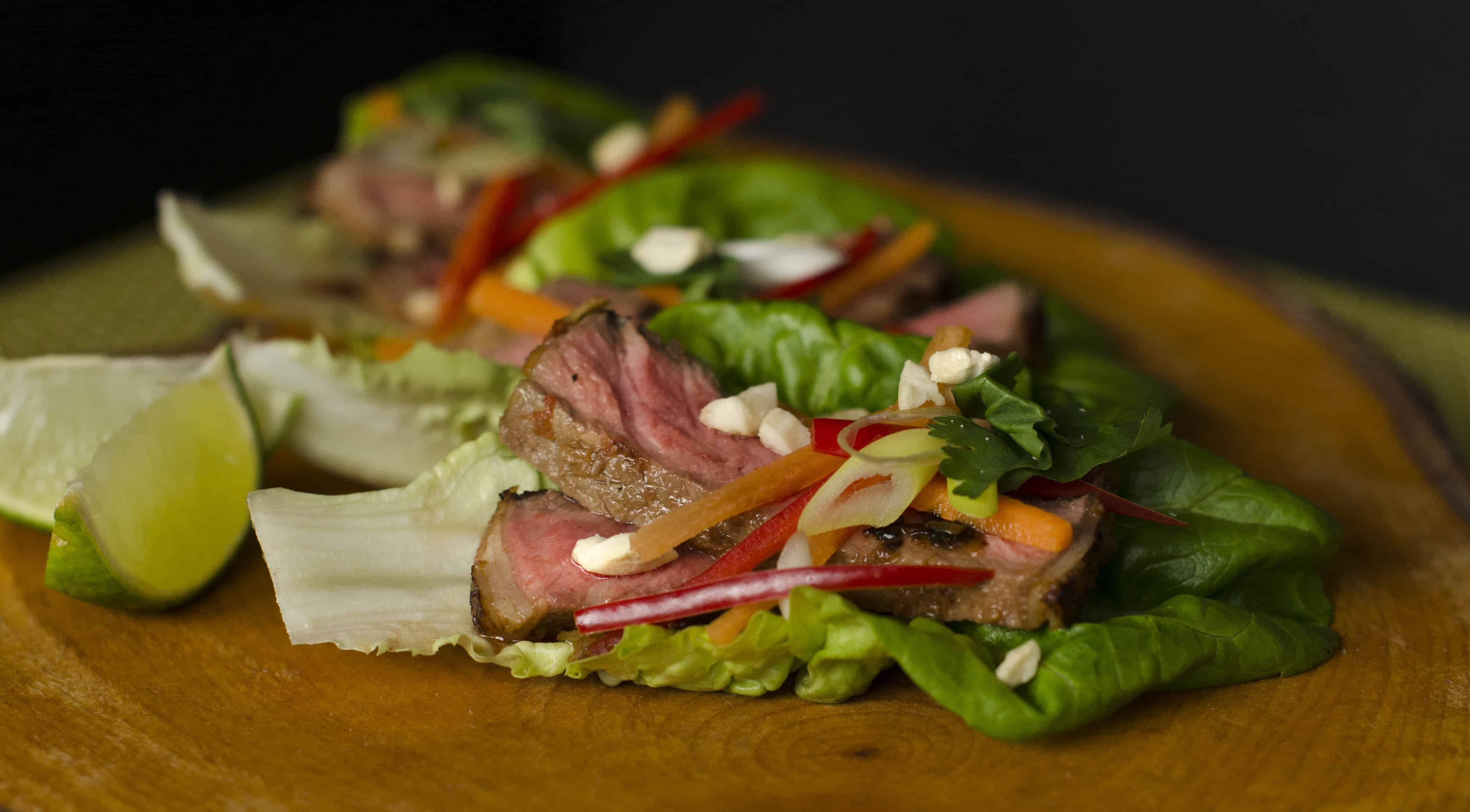 beautfully medium rare slices of sirloin steak marinated in a lemongrass rub served on lettuce leaves and topped with chillis and spring onions and a slice of lime on a wooden chopping board.