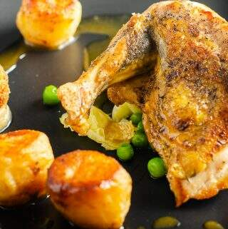 A close up of guinea fowl supreme with pan fried green served with a chicken leg bonbon, fondant potatoes and chicken jus