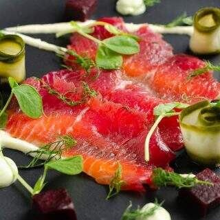 A closeup view of a black matt plate serving of sliced beetroot cured salmon on top of a horseradish cream with cubes of beetroot, slices of pickled cucumber rolled and avocado dil cream served around the plate and finished with fresh dill and pea shoots.