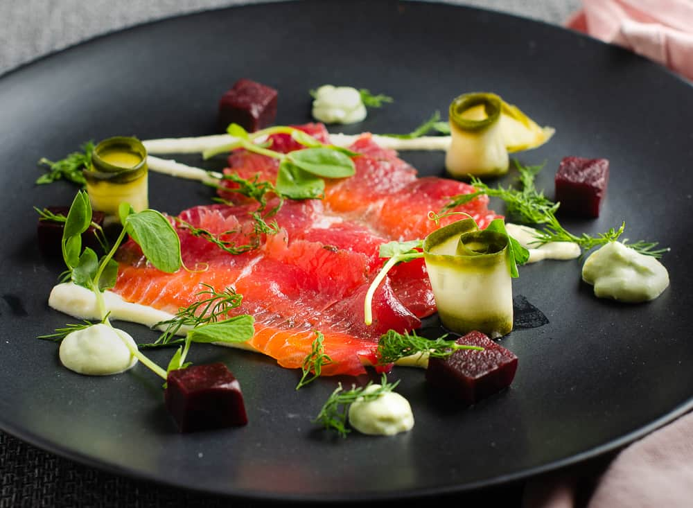 A lovely inviting plate of beetroot cured salmon slices, served on a black plate with a drizzle of horseradish cream, and surrounded with extras like cubed cooked beetroot, slices of rolled pickled cucumber and an avocado dill cream then topped with fresh herbs like pea shoots and fresh dill.