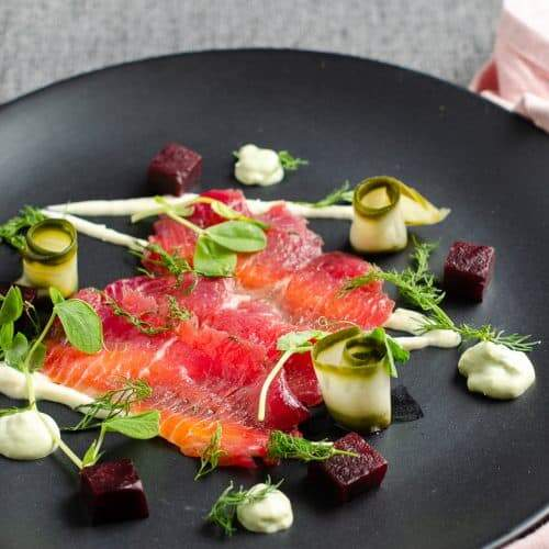 A stunning black plate with slices of beetroot cured salmon, cubed beetroot, a drizzle of horseradish cream, rolled slices of pickled cucumber, dollops of avocado dill cream and topped with fresh sprigs of dill and pea shoots.