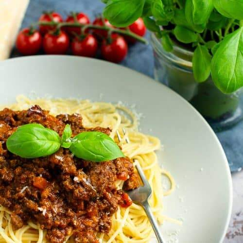 A pale grey plate filled with spaghetti bolognese topped with basil leaves and fresh tomatoes and basil in the back.