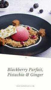 A blackberry parfait dessert served with oat and ginger crumb, a swirl of yogurt, some blackberry curd, fresh ginger cake and topped with pistachio meringue on top of a white border with the dessert name.