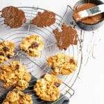 A circular metal cooling rack topped with sugary florentines, some coated in chocolate with a small tub of melted chocolate and pastry brush behind