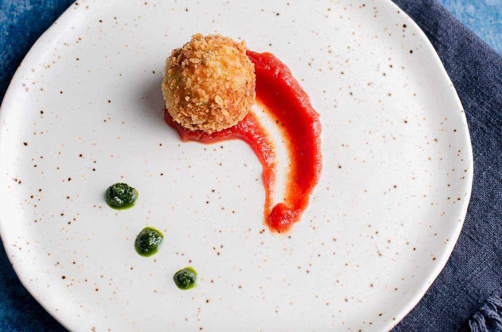 A top down view of a deep fried potato & cheese ball served on top of a rich tomato sauce with dollops of basil puree on a ceramic plate resting on a denim blue linen napkin.