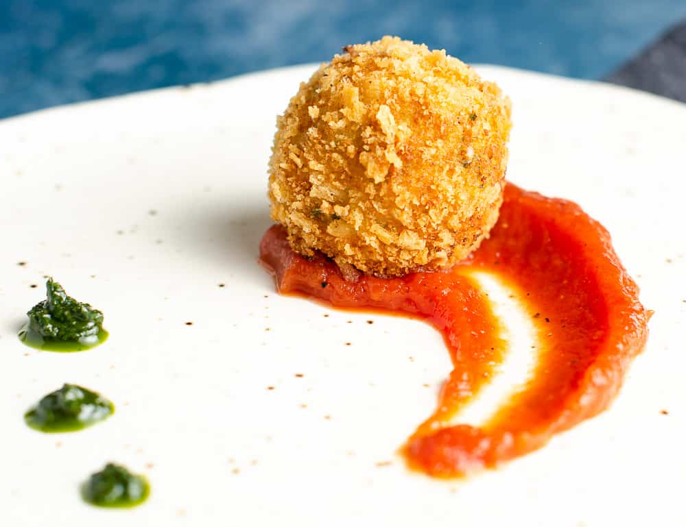 A Closeup view of a deep fried potato & cheese ball served on top of a rich tomato sauce with dollops of basil puree on a ceramic plate with specks of brown and a blue backdrop.