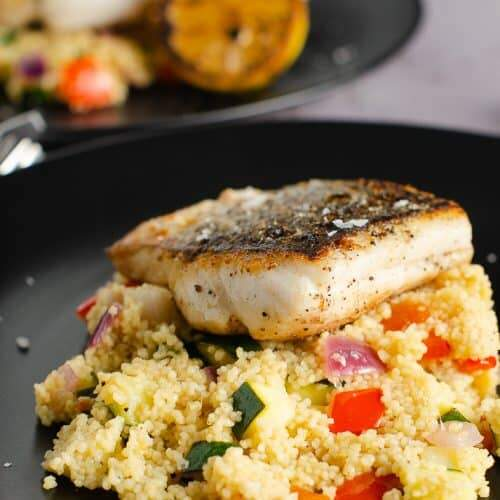 A piece of pan fried hake on a bed of lemon couscous filled with red peppers and courgettes, on a black plate and a seared lemon on the side.